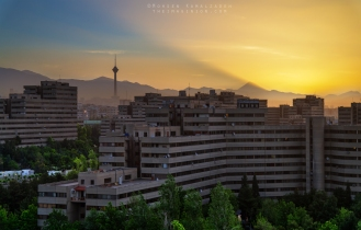 Dawn at the Ekbatan Complex in Tehran, Iran. The mountain creating the gigantic light shaft is mount Damavand.